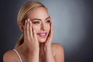 photo of woman tightening skin on face with hands, giving an anti-aging effect like microneedling