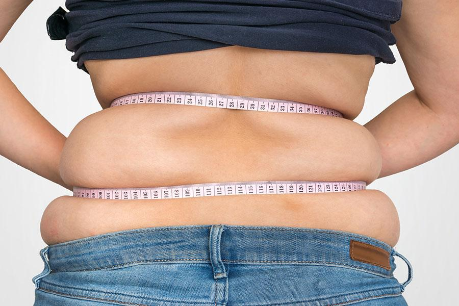 Overweight women with measuring tape taking a naturopathic approach to weight loss