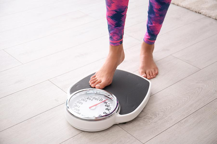 Woman measuring her weight using scales on floor